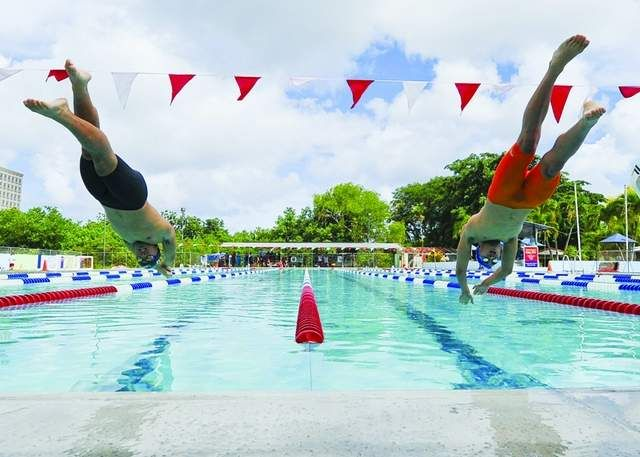 Take your mark, go: Swimmers Alexander Gonzales, 14, left, and Tomas Bonsembiante, 17, spring from their starting blocks at the start...