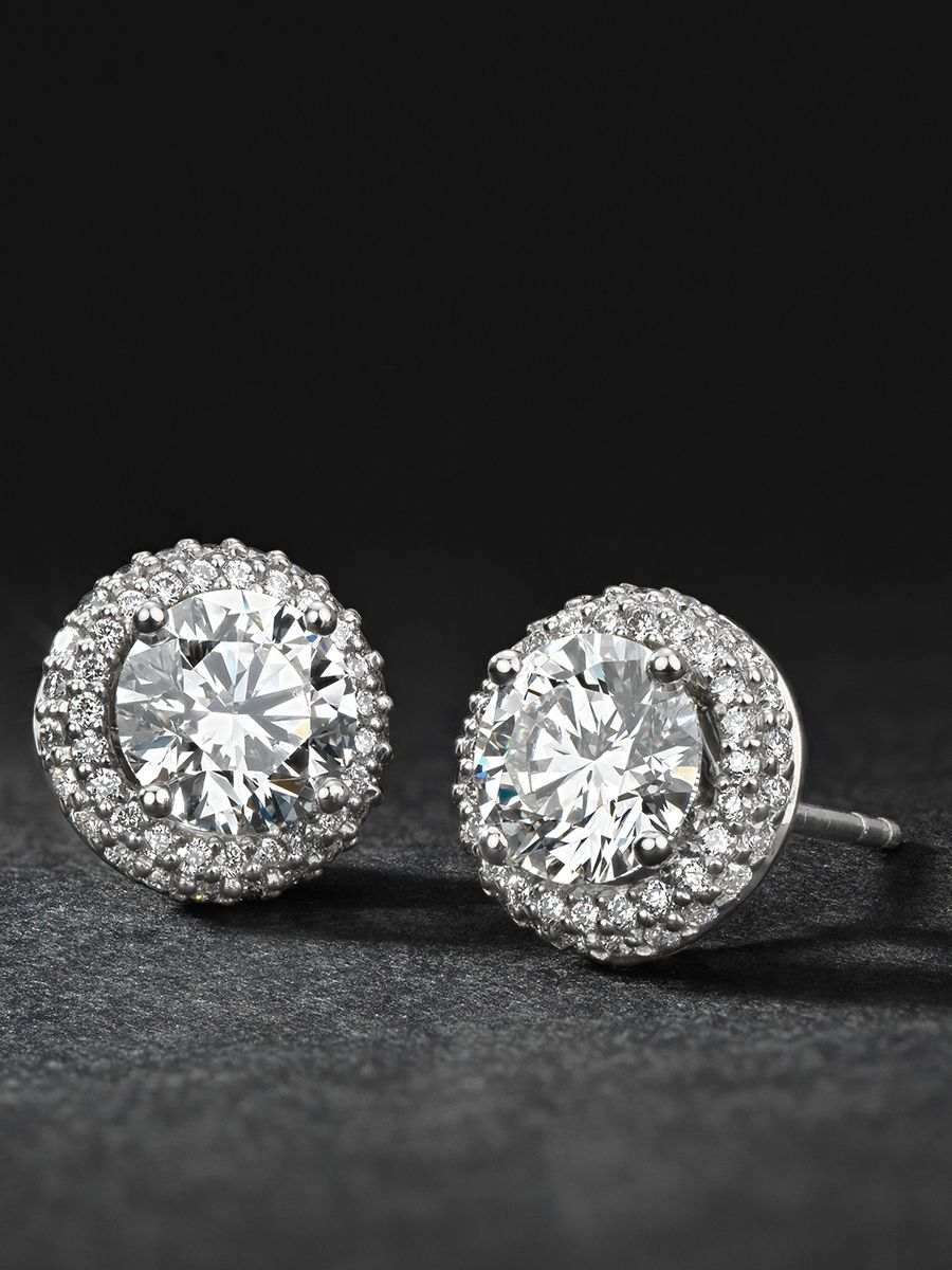 9e0330932 Add some sparkle to your style with these diamond stud earrings, showcasing  round diamonds accented with a halo of brilliant pave-set diamonds in  platinum.