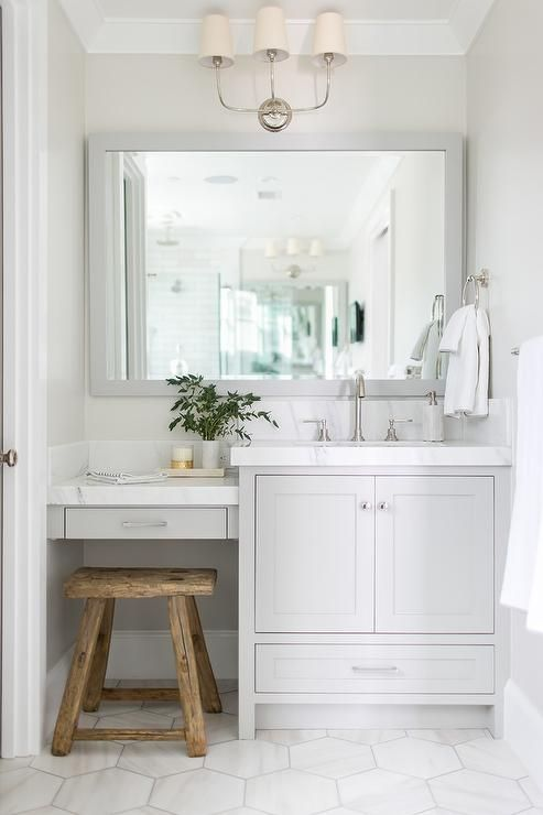 Charming white and gray bathroom boasts a rustic wood stool placed on large white marble hex floor tiles beneath a light gray drop down built-in makeup vanity topped with a thick white marble countertop fixed against a white marble backsplash.