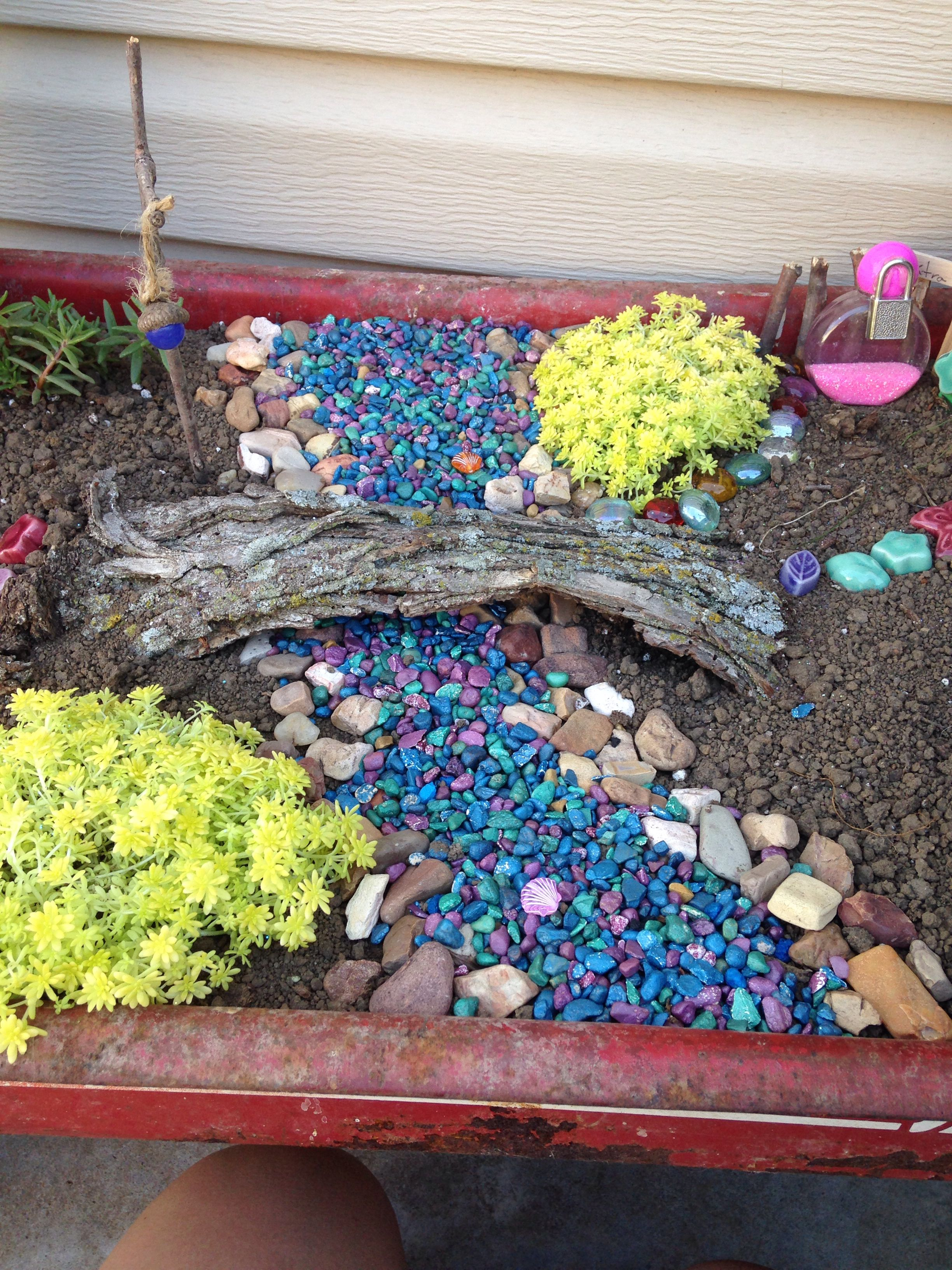 This is a stream made of colored pebbles with a bridge over it.