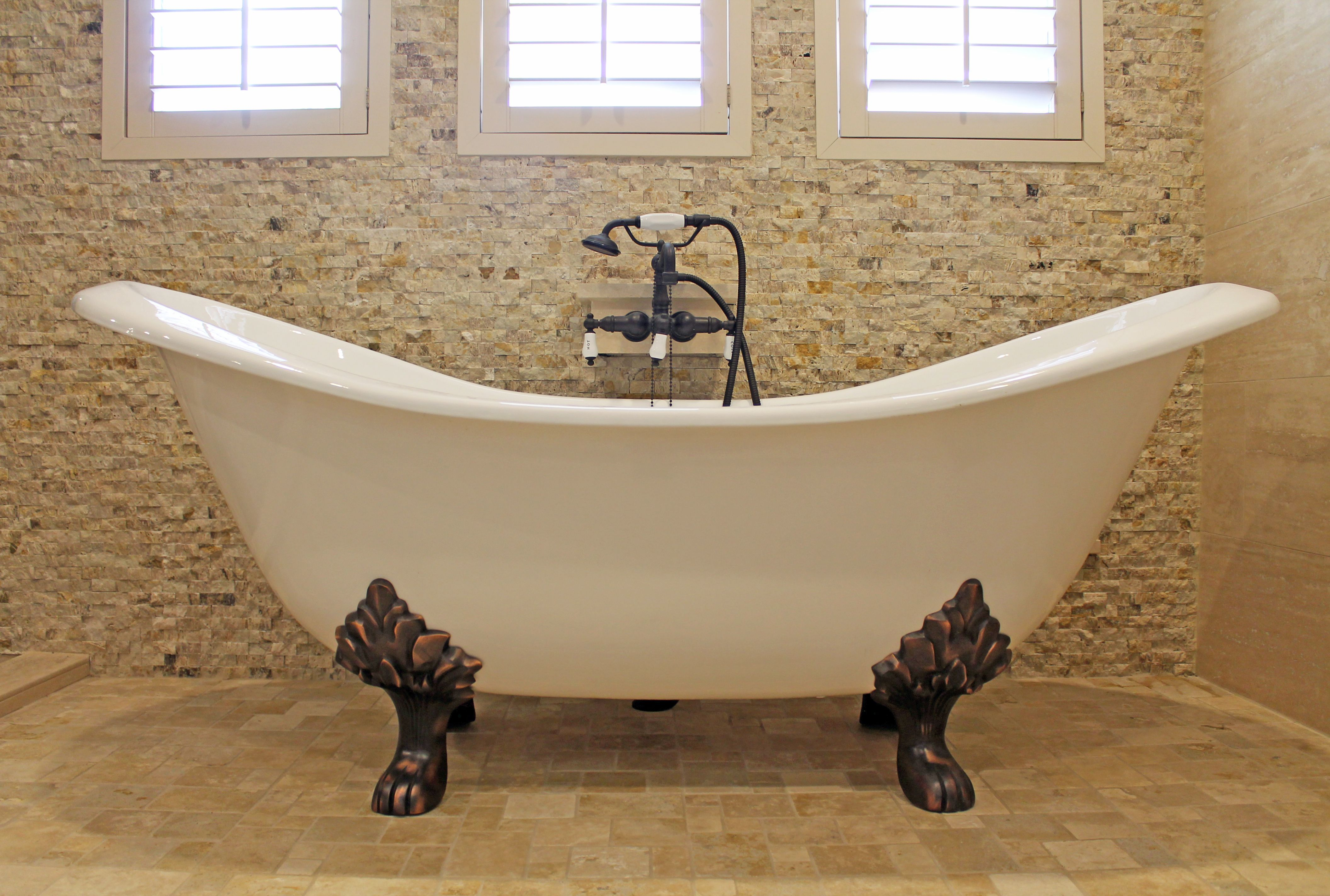 Freestanding tub with bronze legs and natural stone tile. #bathroom ...