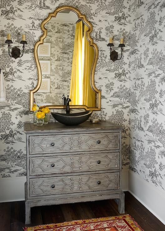 French Bathroom Features Walls Clad In Black And White Toile Wallpaper Lined With A Gold Mirror Illuminated By Sconces Over Gray Chest Turned
