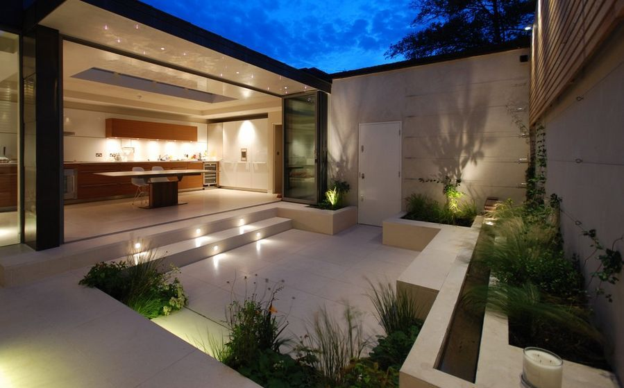 When designing a sunken entertainment area outdoors it's also important to add accent lighting. Strategically placed sconces and spotlights can highlight certain elements and create interesting visual effects at night