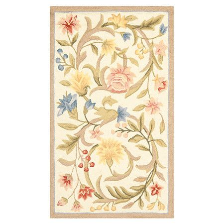 Picture this rug with very light blue walls with white wood trim, pine floors, cream sofas with splashes of red and a touch of yellow.  Hand-hooked wool rug with a floral motif.   Product: RugConstruction Material: WoolColor: Ivory, orang...