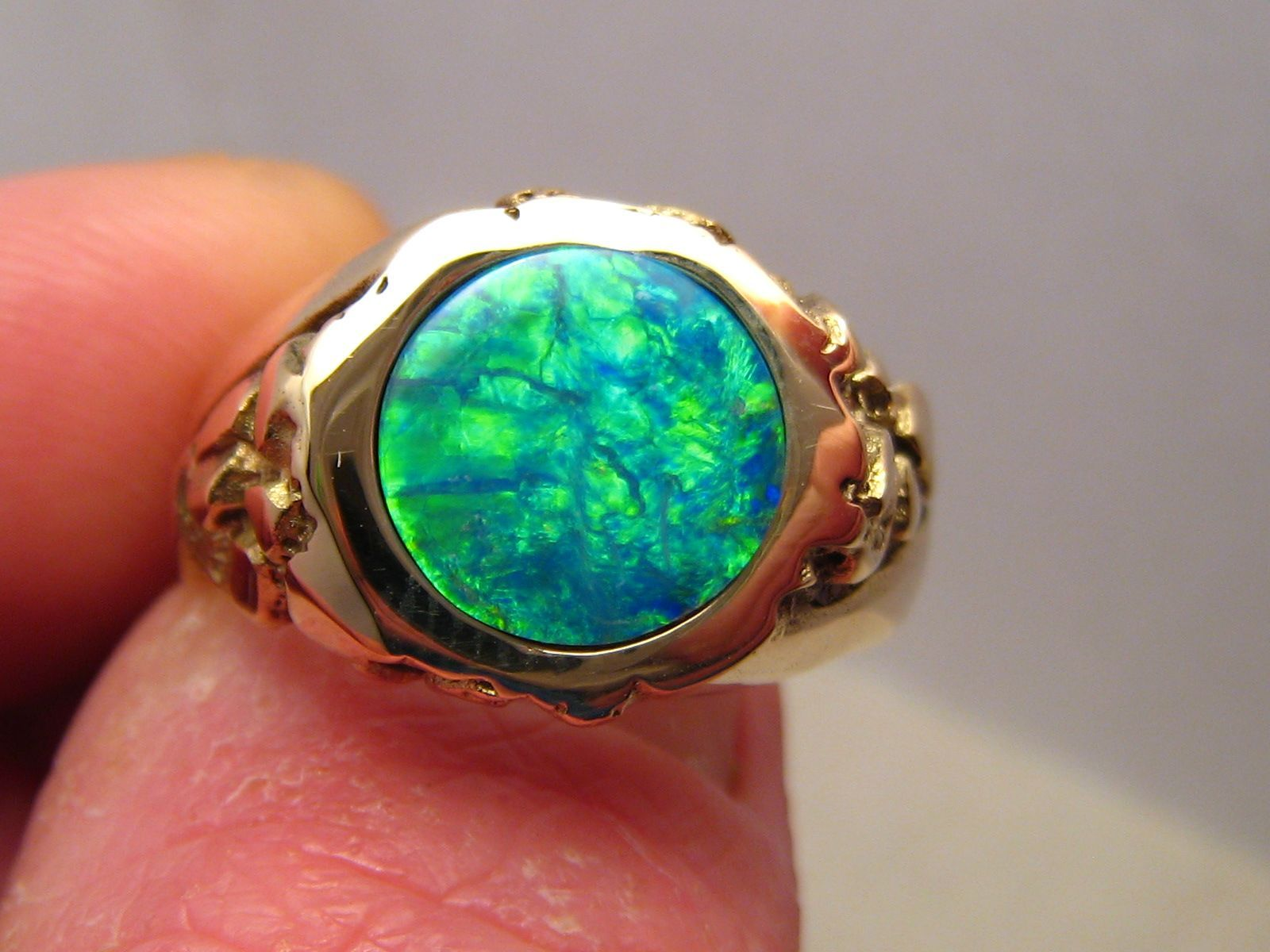 Mens opal ring in a gram k gold textured band with a round