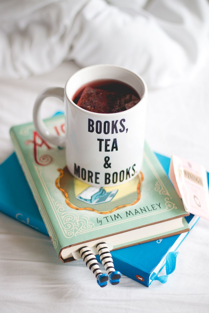 """Foto de Melina Souza. Cama branca com livros Calm e Alice In Tumblr-land com marcadores artesanais de Alice no País das Maravilhas e uma caneca com chá escrito """"books, tea and more books"""" em cima."""