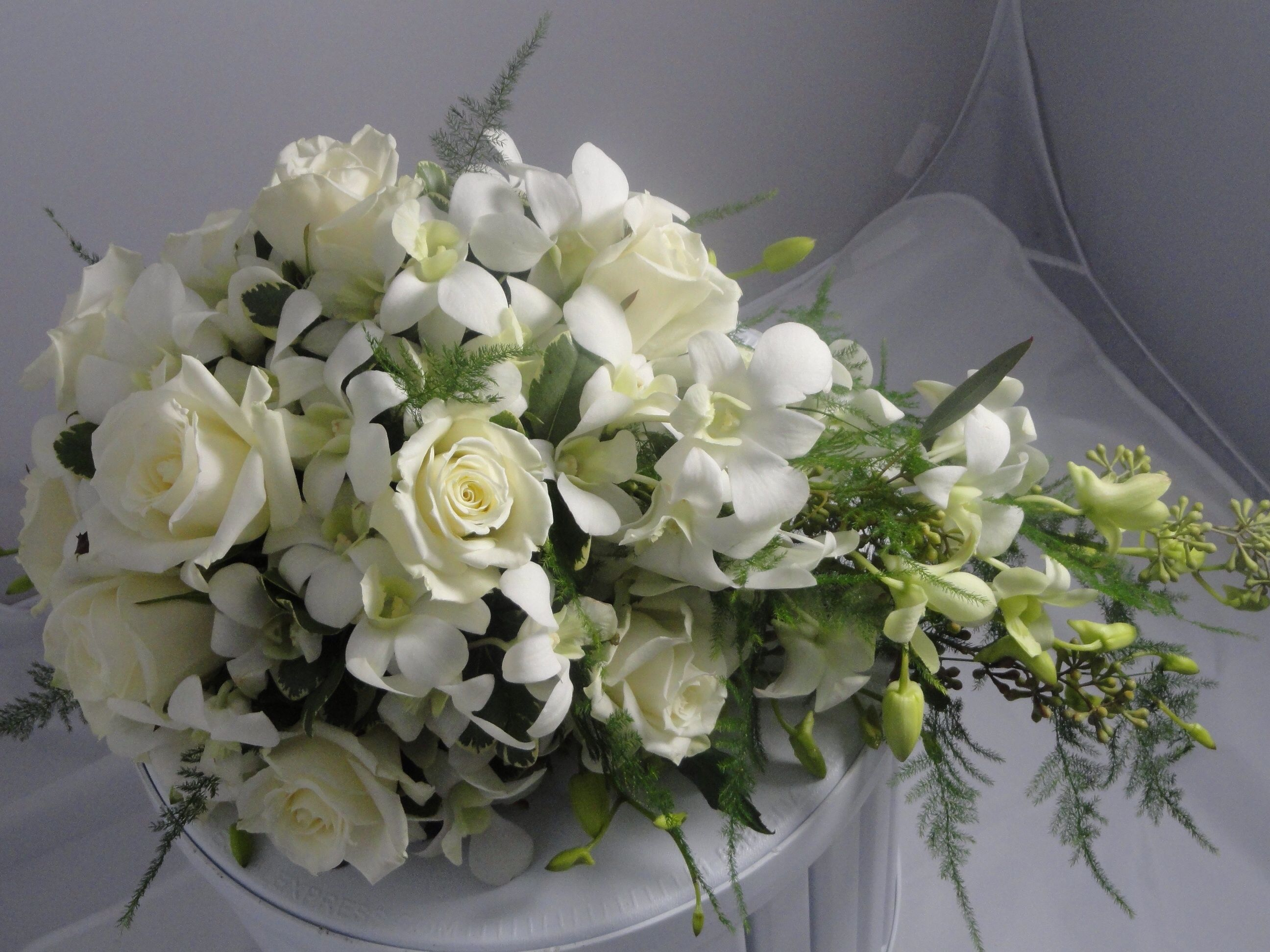 Cascading bouquet in green and white...white roses and white dendrobrium orchids, greens in fern and seeded eucalyptus