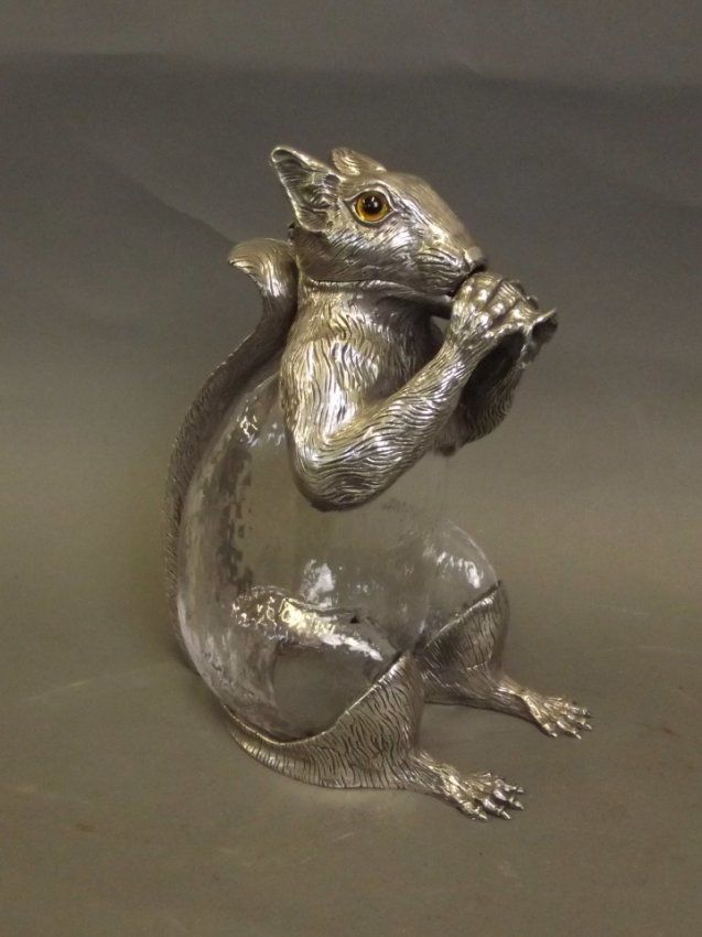 A silver plated claret jug in the form of a seated squirrel.