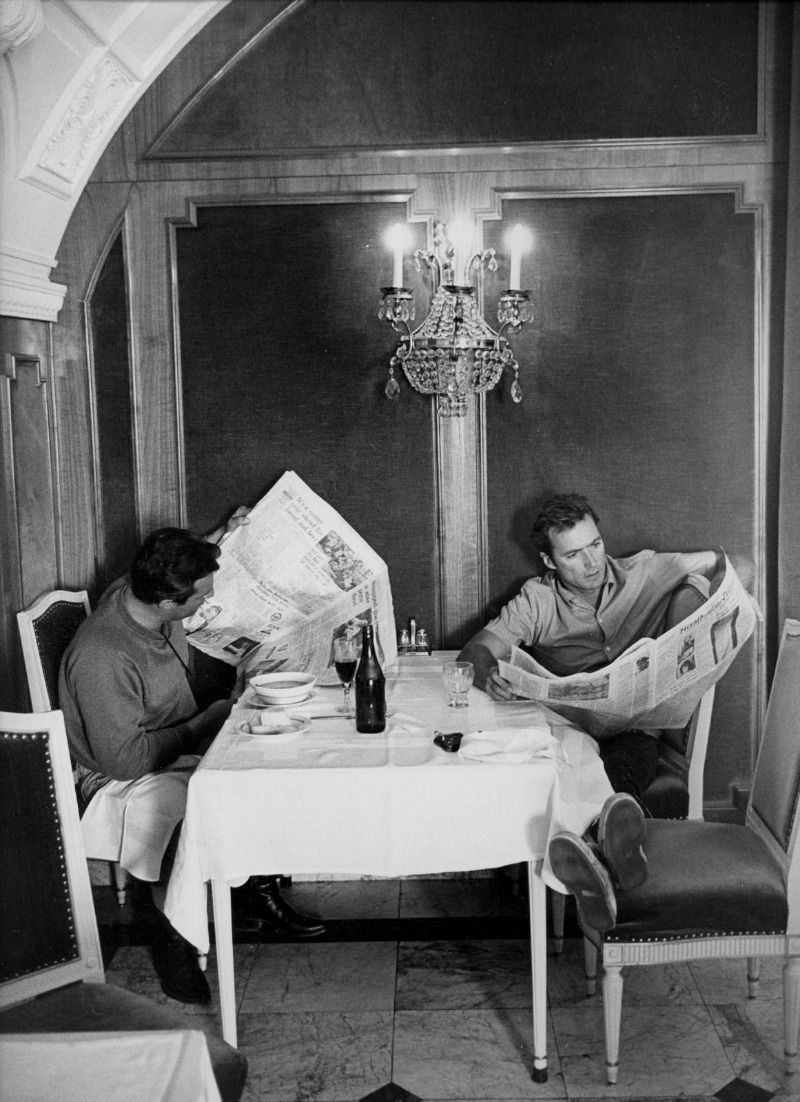 Clint Eastwood is photographed by Lawrence Schiller reading the International Herald Tribune at a restaurant during the making of Where Eagles Dare, 1968.