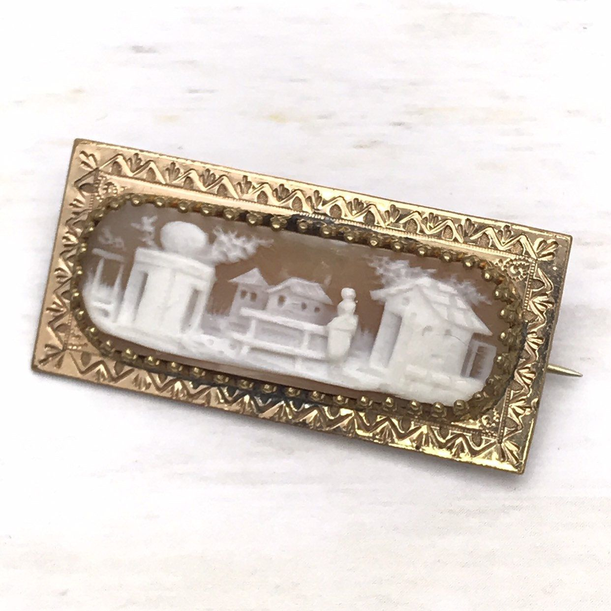 Antique Victorian Cameo Brooch Rebecca at the Well Pin,   This stunning and very unusual cameo brooch dates from the mid to late 1800s. Victorian in motif and design, it depicts Rebecca in the garden, crossing a bridge to a Memorial building. She leaves behind her home. The landscape includes the roof of other homes in the background and distant city towers on the left. It even has clouds in the sky, it is expertly carved.  The lovely carving is bezel set, the setting is a delicate crown bezel w