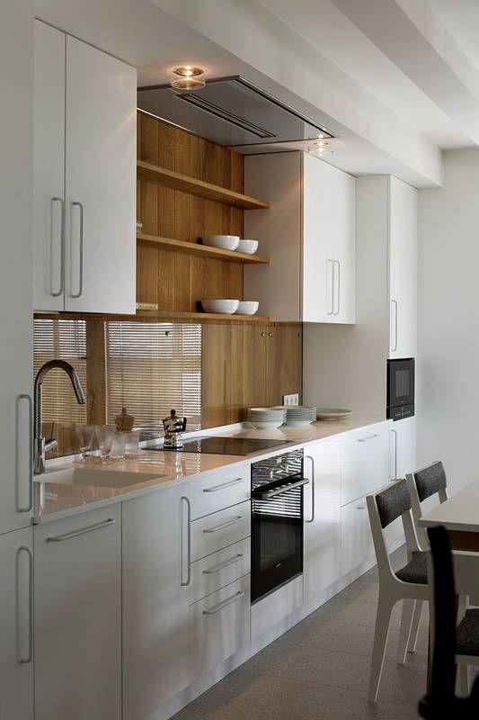 Ściana nad blatem wyłożona deskami w ciepłym odcieniu uszlachetniła tę białą kuchnię. Drewno zabezpieczono przed działaniem wody i zatłuszczeniem, mocując do niego ozdobnymi śrubami szklane ekrany. Wyciąg kuchenny wbudowano estetycznie w podwieszany sufit.