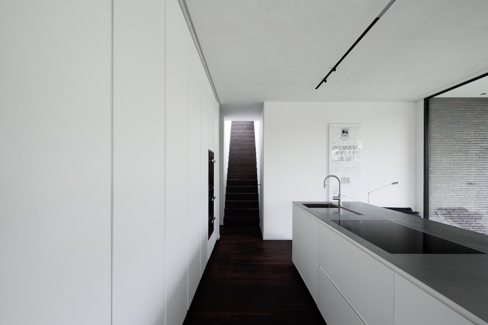 Strakke Witte Keuken : Wengé parket loopt door in trap strakke witte keuken met inox
