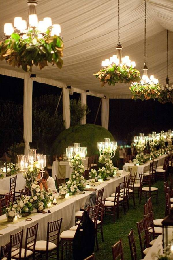 Long table party or reception centerpieces and lighting decor a bit over the top for my taste but love the use of magnolia leaves with the chandeliers