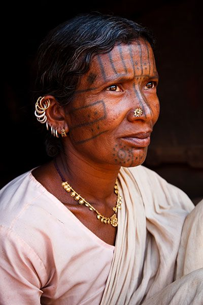 India | Portrait of a Kutia Kondh tribal woman with traditional piercings and facial tattoos, in a small village near Baliguda. Orissa  | © Kimberley Coole