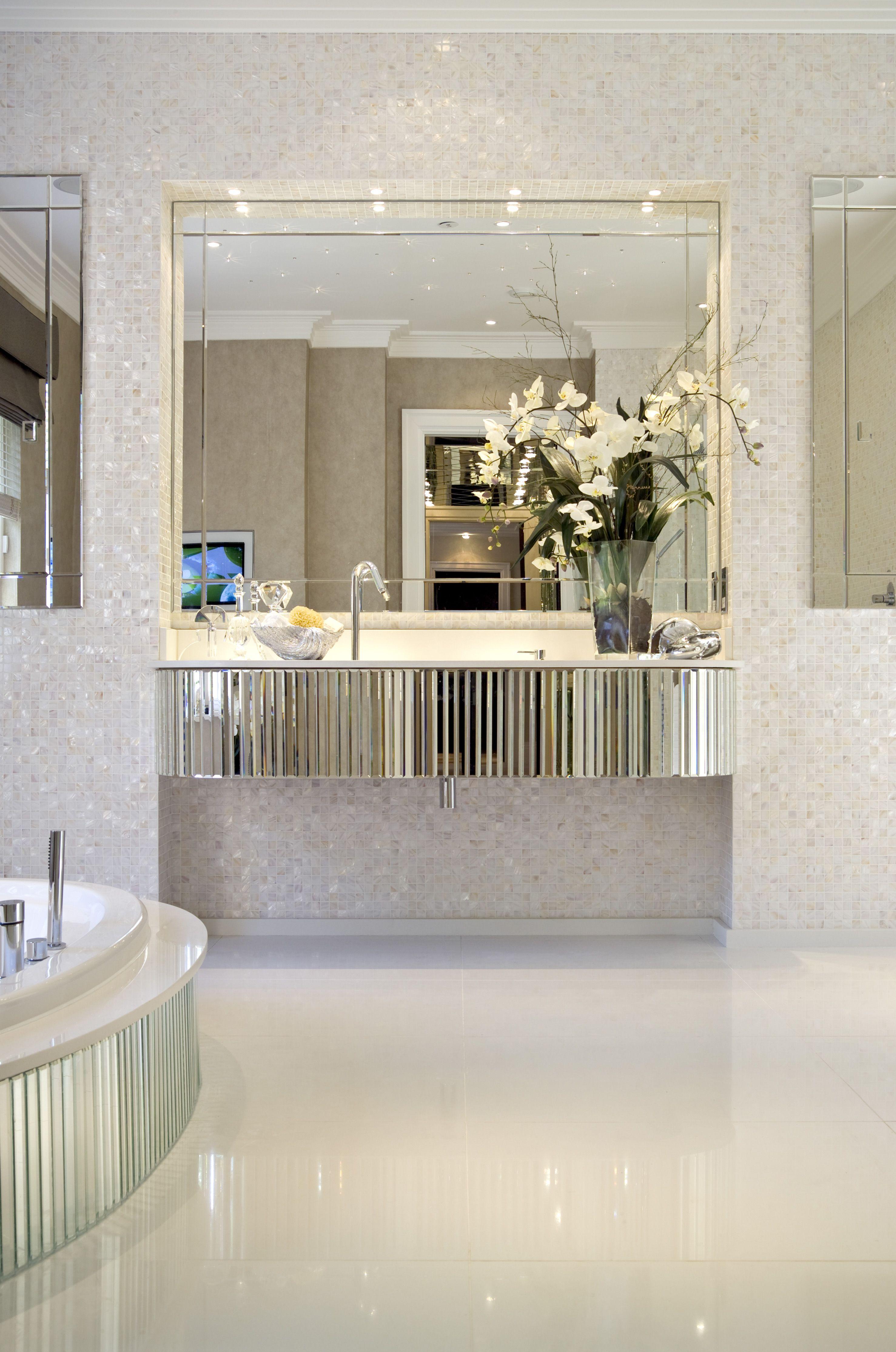 bevelled mirror floating vanity unit and semisunken bath create art deco glamour in master