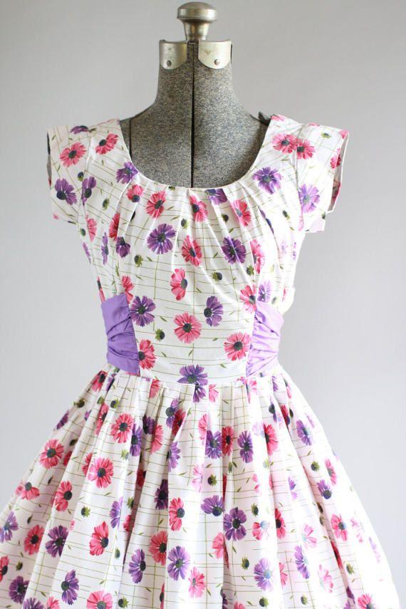 7aed01bf10e515 Deze jaren 1950 katoenen jurk heeft een mooie roze en paarse bloemenprint.  Kap mouwen. Gesmoord taille. De taille is versierd met een paarse taille  sjerp ...