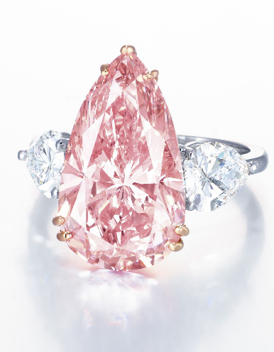 A MAGNIFICENT COLOURED DIAMOND AND DIAMOND RING Set with a pear-shaped fancy intense pink diamond weighing approximately 9.38 carats, flanked by pear-shaped diamonds, mounted in platinum and 18k rose gold. ( Estimate of approx $5-8 million ..)