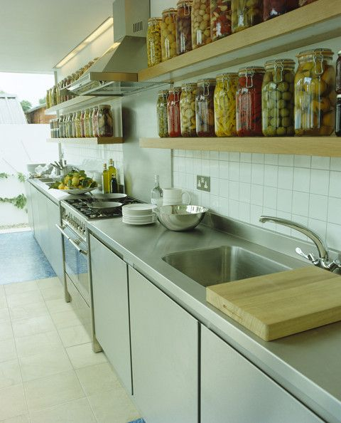 Understated handle-less kitchen cabinets. Chunky open shelving with rows of jars on display
