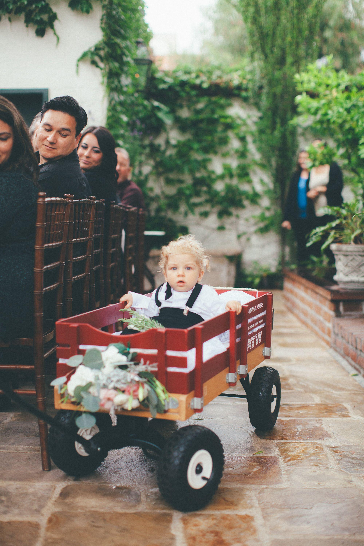Ring bearer pulling infant ring bearer in wagon photographer