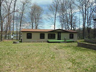 #4203-785 W LONG LK. DR. Nice 84 manuf. Home on canal on Long Lk. with 3 Bdrms., 2 baths, fireplace, sun room, decks, cent. Air, 2 car garage, boat house, great view, boat slit & dock. Only $110,000.