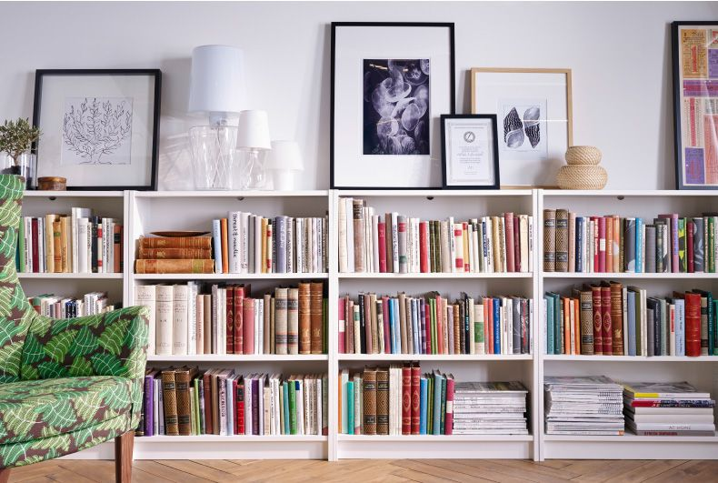 A row of IKEA bookcases lines a wall. On top is framed art and lamps ...