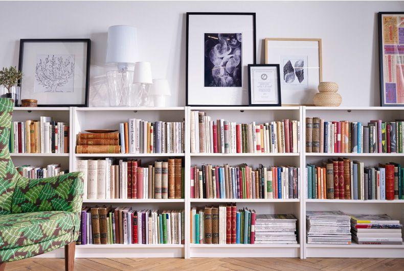 Libreria Sopra Letto : Fila di librerie alla parete cornici e lampade sopra le librerie