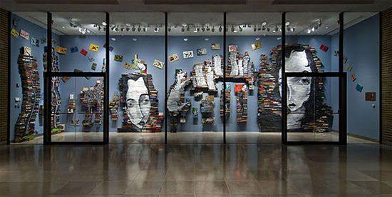 """O Artista Mike Stilkey faz pinturas artísticas nos montes de livros empilhados. Sua arte é chamada de esculturas """"livro"""". Stilkey usa tinta acrílica e lápis coloridos para formar uma imagens que lembra o expressionismo alemão."""