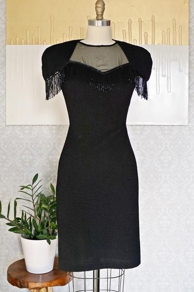 Daring vintage 1980's dress. Simple cut with sheer neckline and short, capped sleeves which are embellished withbeaded fringe. Open, teardrop back is sultry an