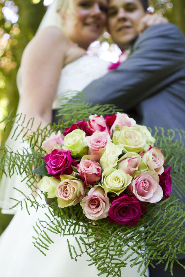 Mooi boeket, met bruidspaar op de achtergrond.