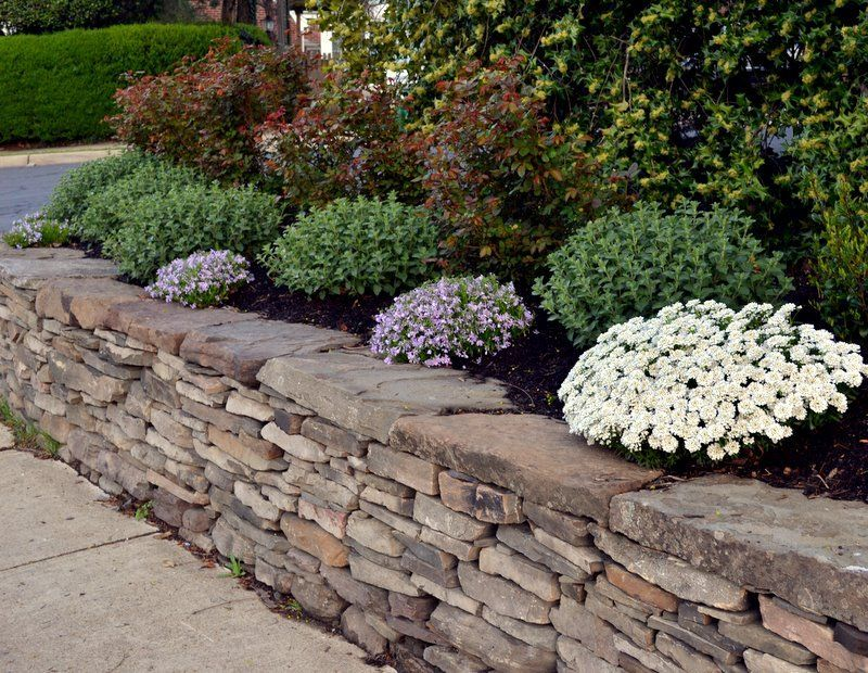 Dry Stacked Fieldstone Retaining Wall And Plantings Designed By