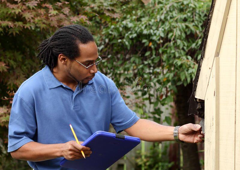 Insurance adjuster inspects shingle damage an insurance