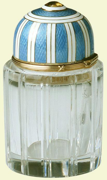 Cylindrical scent bottle of fluted rock crystal, mounted with red-gold reed and ties, the hinged domed cap of bright blue guilloché and white enamel stripes with a brilliant topaz finial; inside is a glass stopper. Mark of Feodor Afanassiev; gold mark of 56 zolotniks, 1917. Given to Queen Mary by Tsarina Marie Feodorovna.