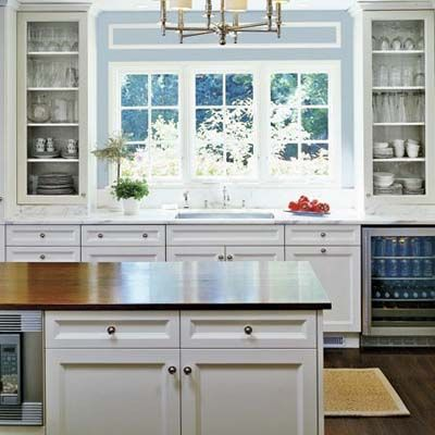White Cabinets, Blue Walls; Wood Countertop On Kitchen Island With Window  Over Kitchen Sink