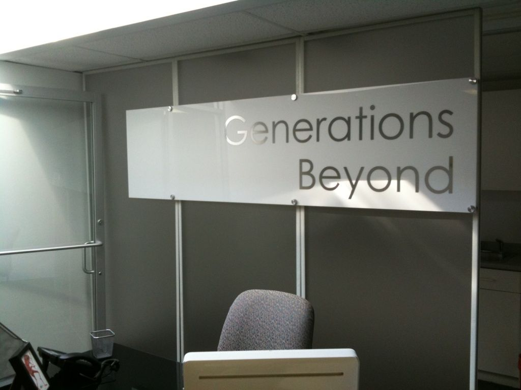 Custom office/lobby partition wall fabricated from aluminum and frosted acrylic. White acrylic with silver letters mounted with brushed aluminum stand offs.