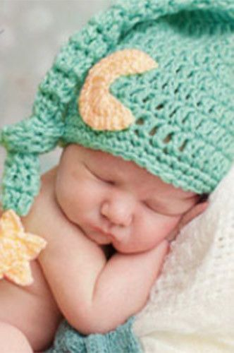 bb3d97453 This mint green knit hat has soft yellow moon and a yellow star at the end  of the hat to add some character. In a photoshoot for children baby hats  play an ...