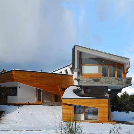 This mountainside house by G2 Estudio in Argentine Patagonia is wrapped in a stone and wood facade.