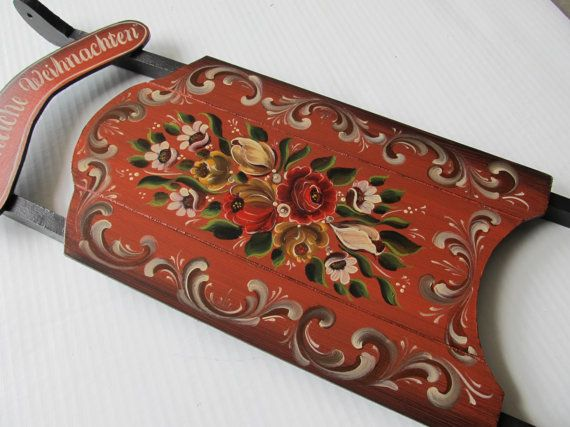 Beautiful German Bauernmalerei hand painted on a bass wood sled....with a black and red background. The flowers are in colors of reds, yellows, greens and whites. White and brown scrolls surrounding the center piece. Hand painted lettering reading Fröhliche Weihnachten! meaning Merry Christmas in German. The dimensions are approximately 9 wide by 23 long. The style, translation, my name and date (Cathy Koball 2014) are hand painted on the back. Several coats of bees wax cover it for its p...