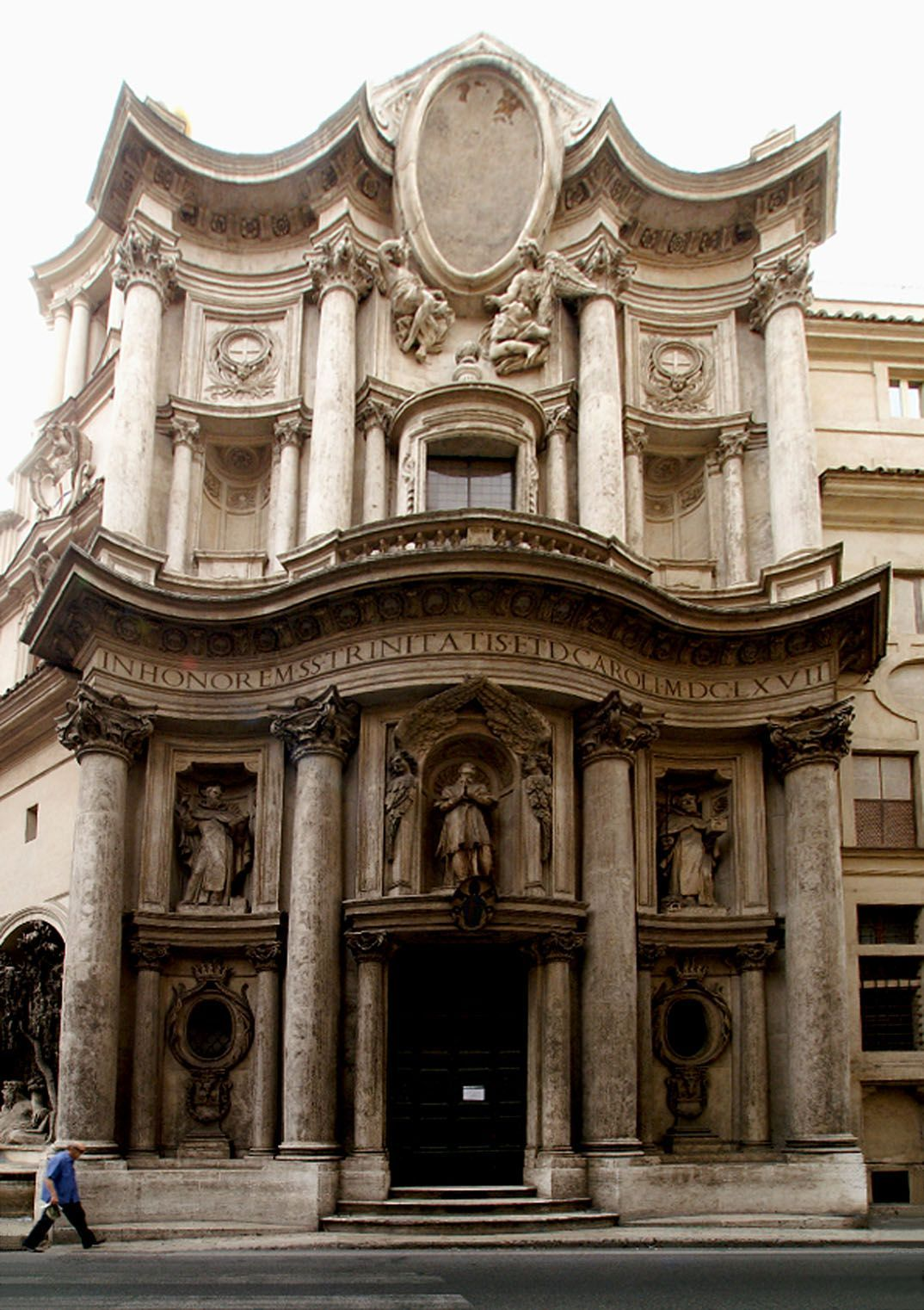 This piece of architecture was an influential Baroque church in Rome that was designed by Francesco Borromini as part of a small monastery for a community of Spanish monks. It was commissioned in 1634 and was built during 1638–46, except for the tall facade, which was added about 1677. Its floor plan was in the shape of a Greek cross.