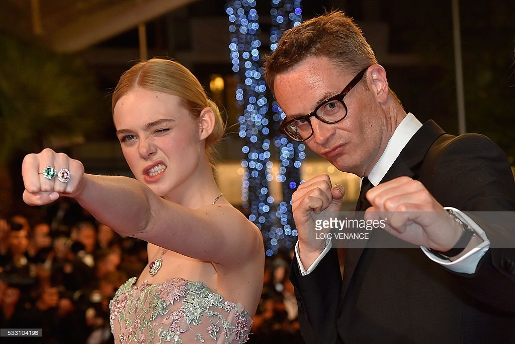 TOPSHOT - Danish director Nicolas Winding Refn (R) and US actress Elle Fanning pose as they arrive on May 20, 2016 for the screening of the film 'The Neon Demon' at the 69th Cannes Film Festival in Cannes, southern France. / AFP / LOIC