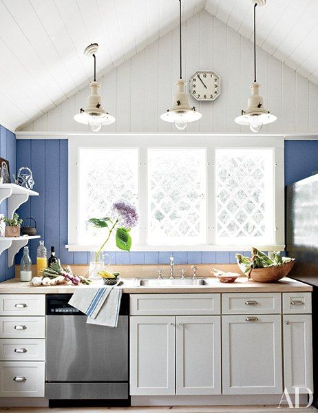 At artist Ahn Duong's Hamptons cottage, the kitchen features a gabled ceiling. The walls are painted in a Farrow & Ball blue.
