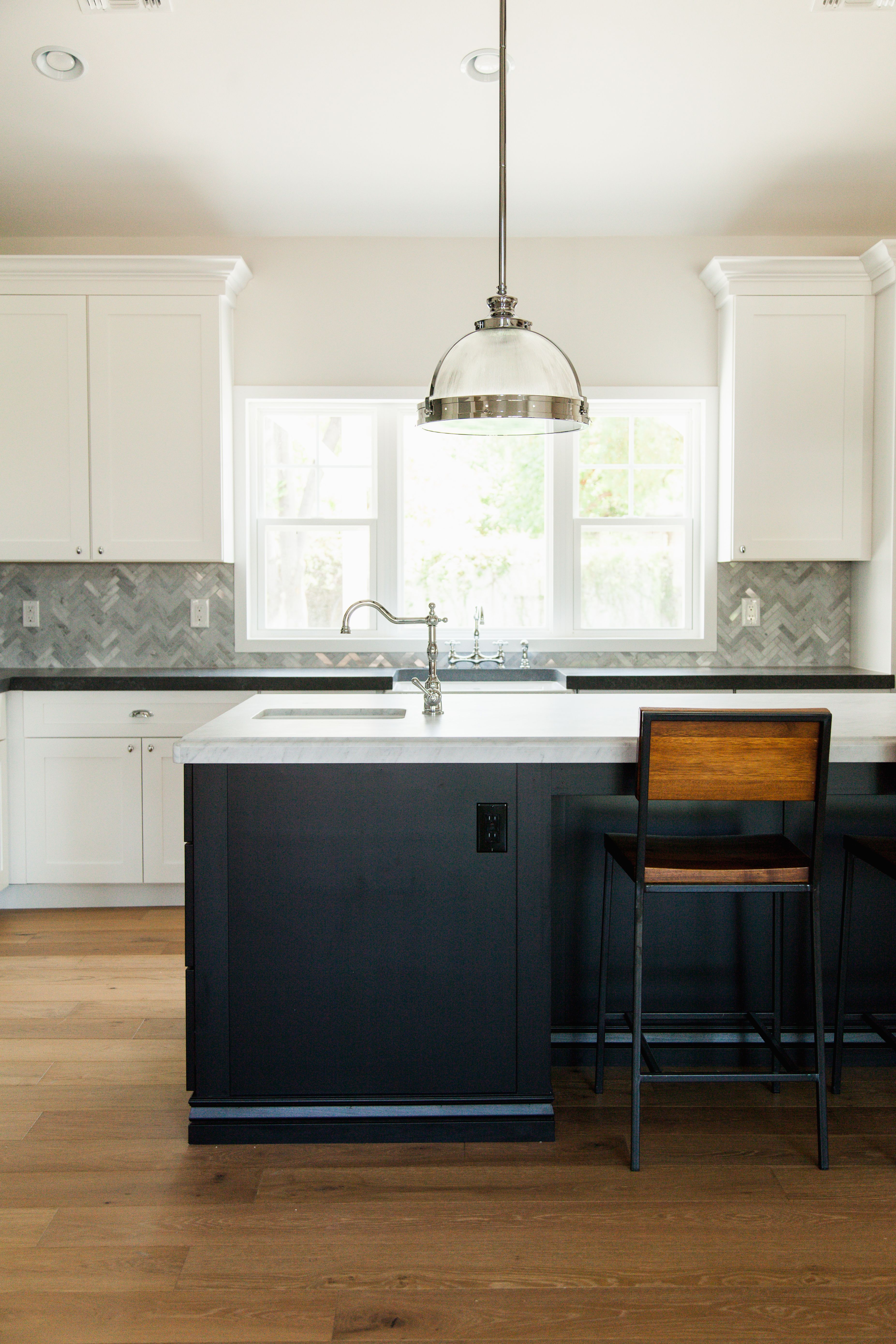 Custom kitchen with black island cabinetry and white perimeter ...