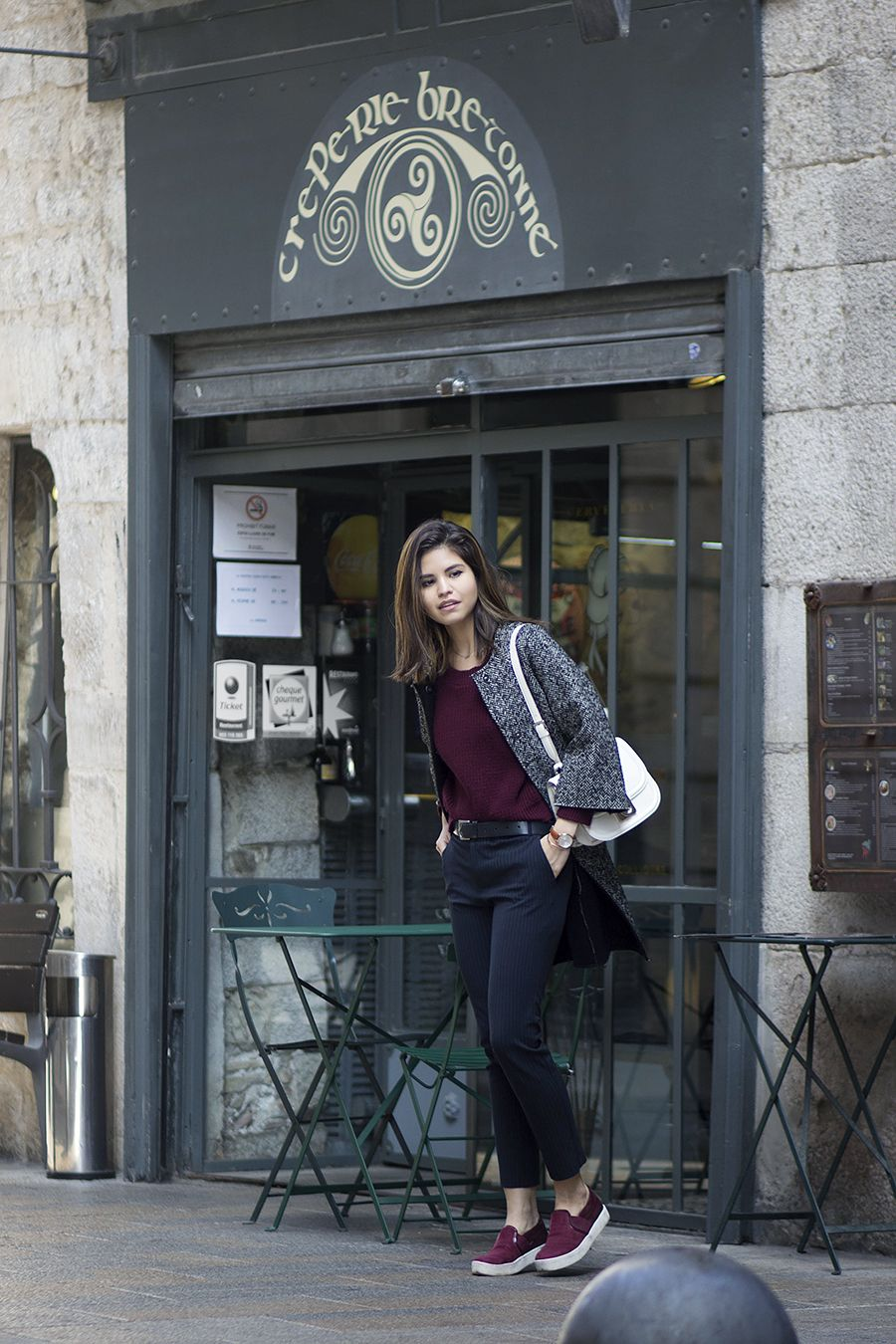 Burgundy knit, ankle trousers, salt and pepper coat, burgundy slip-on sneakers and cream purse.