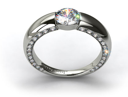 Modern tensionset engagement ring with a thick bar shank and pave