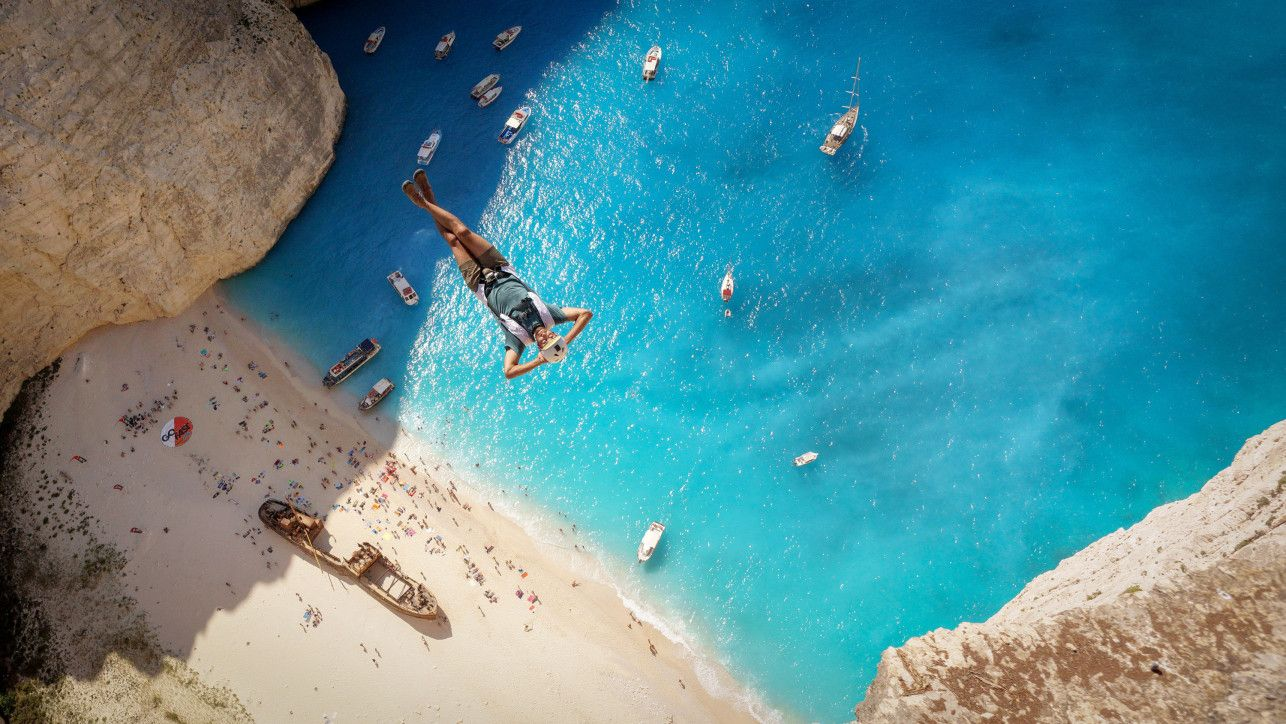 This Man is relaxed as he jumps over Navagio Beach, Greece.