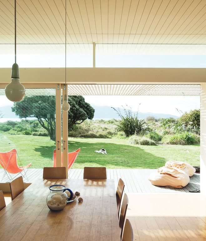 The bach's beachfront site is nestled behind sand dunes with views on