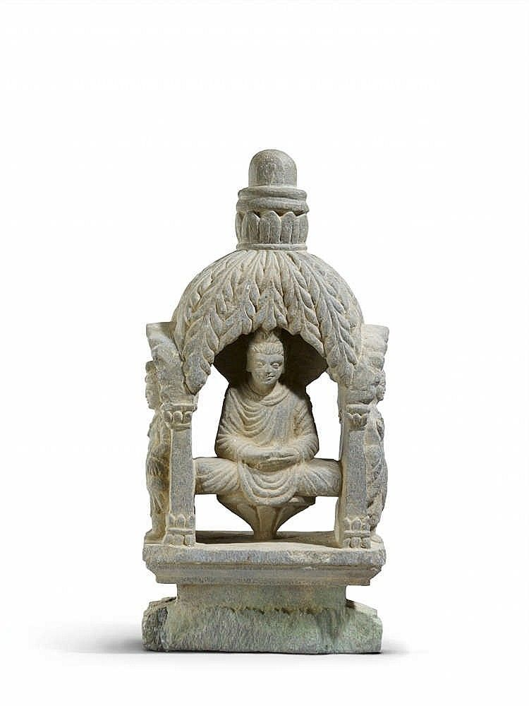 Gandhara grey schist votive stupa of rectangular crosss section, with two Buddhas seated in meditation on a lotus, the hands in dhyana mudra, underneath a canopy of foliage, surmounted by a stupa, to the narrow sides a bodhisattva standing underneath an arch supported by two columns, the former right hand in abhaya mudra, the left hand holding a bottle, above a lotus petal base on a rectangular plinth. Base damaged and restored. 2nd/3rd century.Dimensions: Height 47 cm; width 22 cm