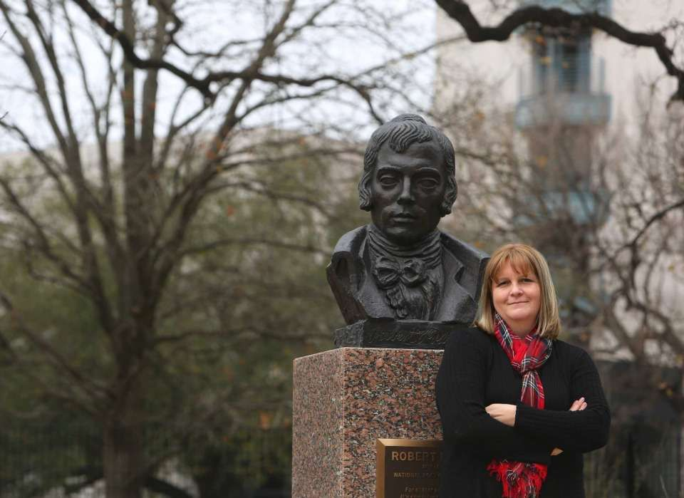 "Writer Caroline Leech stands next to a bust of Scottish poet Robert Burns on Friday, Feb. 3, 2017, in Houston. Leech, who's from Scotland, is debuting her first novel this week, a Young Adult book entitled ""Wait for Me."" The book is set during World War II and is about a Scottish girl who falls in love with the German POW assigned to work on her family's farm. (Annie Mulligan / Freelance)"