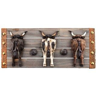 """Put a new meaning to """"turn the other cheek"""" and turn your walls into a place to hang keys, scarves, coats, and purses withThree Steers Wooden Plaque with Hooks. Featuring the backside of three resin steers with hooks, set against a gray wooden plaque, this wall piece will give your home or office an immediate country feel. No buts about it--you need this plaque!        Dimensions:      Length: 8""""    Width: 19""""    Thickness: 2""""    Hook ..."""