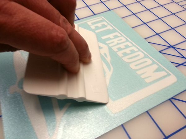 Step 2 using either a squeegee burnisher or credit card rub over the clear transfer tape to ensure decal will transfer