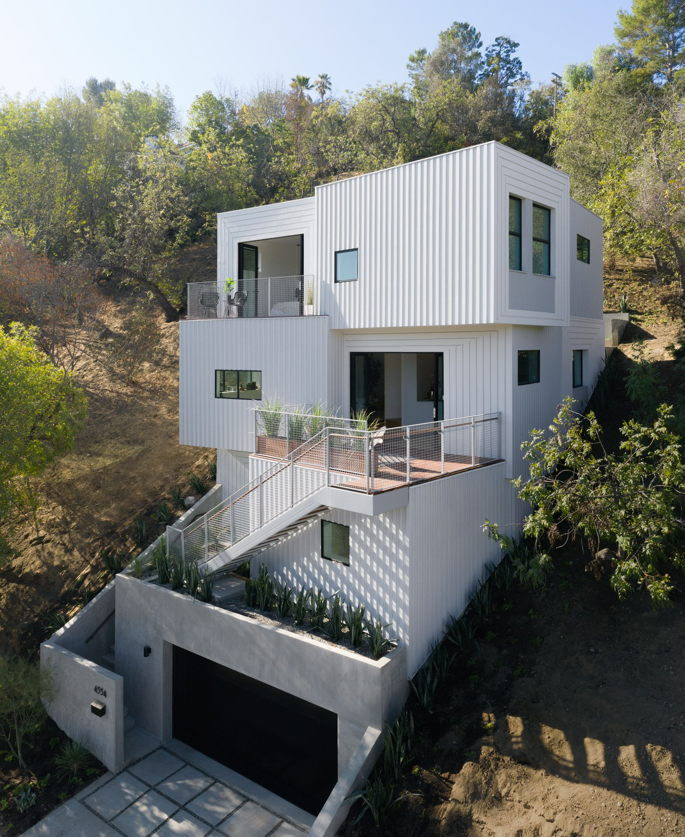 stack house by freelandbuck is lodged into steep hillside in la